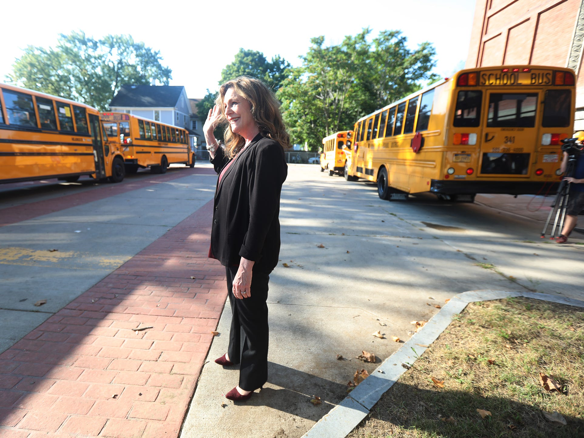 Barbara Deane-Willliams, superintendent of Rochester City School District, watches and waves to students arriving by bus at Rise Community School/Community School #106, formerly School 41 on their first day of school.
