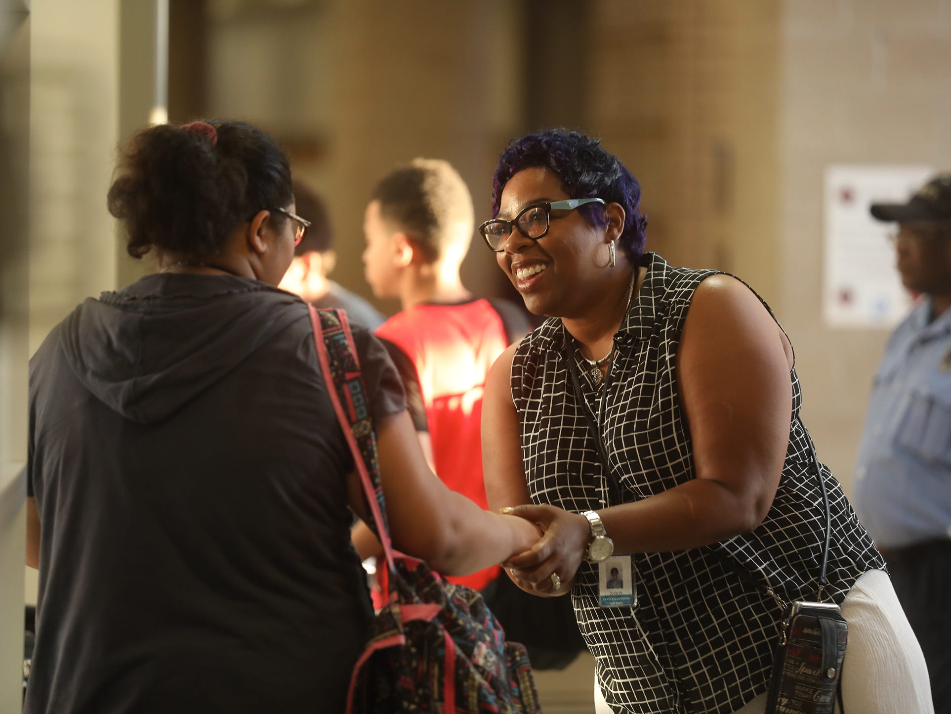 Sherrie Tanner Hammonds, a social worker new to Rochester Early College International High School, greets Yolanda Wooten, a ninth-grader.  Tanner Hammonds shook hands or high-fived students to welcome them to school.