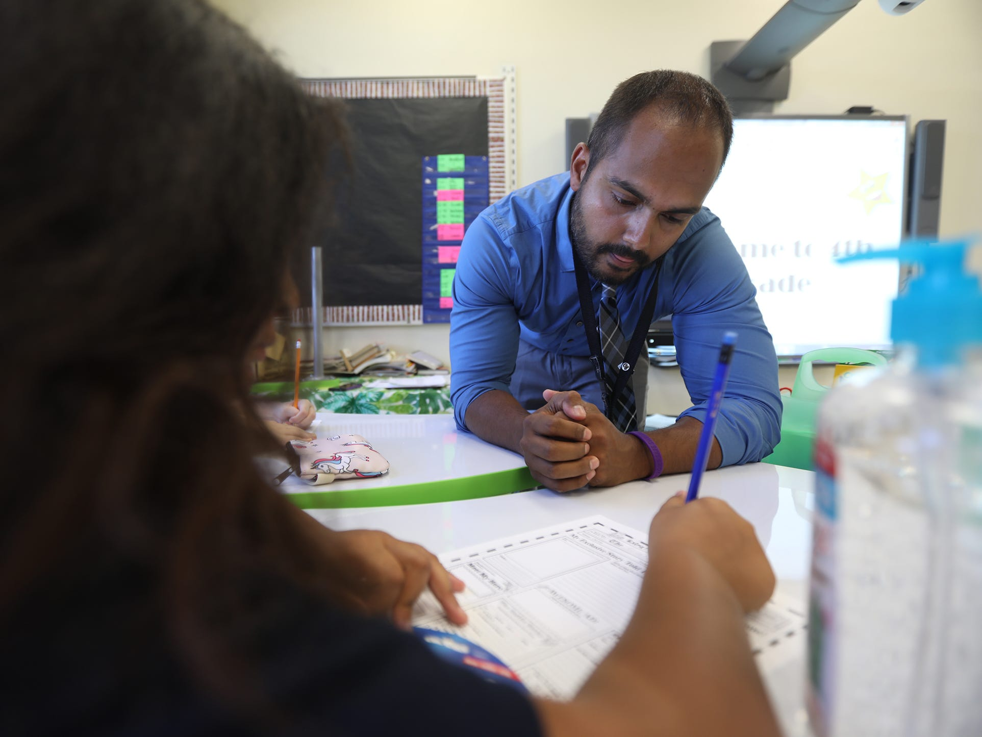 Christopher Smith, a fourth-grade teacher at RISE Community School/Community School No. 106, gets a student started on an autobiographical assignment.  Smith is one of the returning teachers from the former School 41.