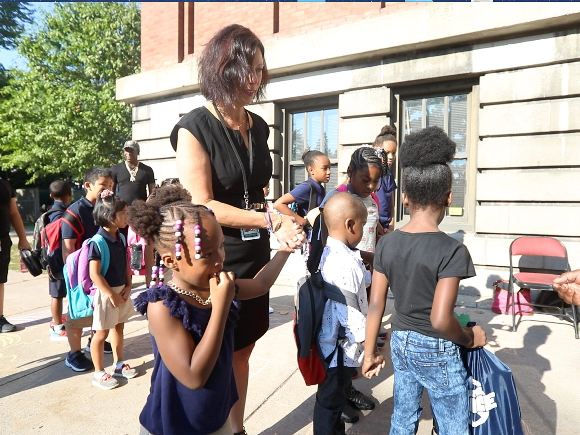 Christine Caluorie-Poles, principal at RISE Community School, helps a younger student enter on the first day of classes.