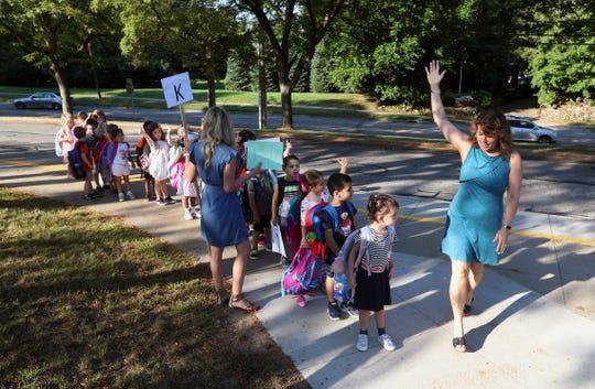 Kindergarten teacher Lori Lusk walks with her students into school  at Allen Creek Elementary School. Pittsford schools have now gone to full-day kindergarten.