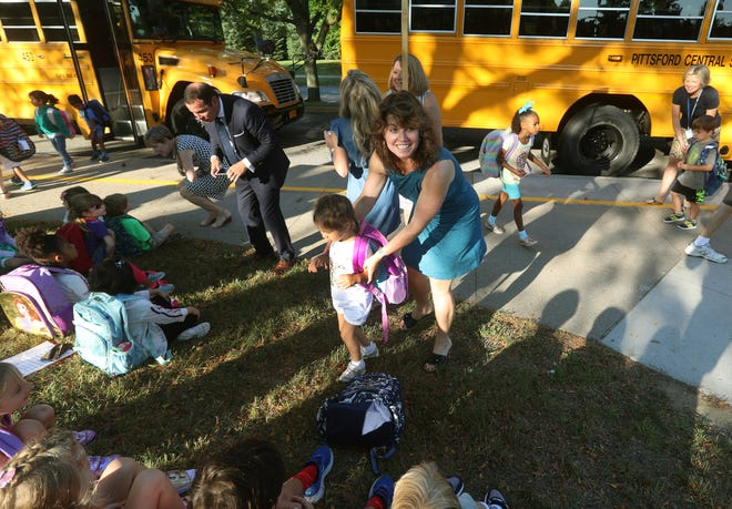 Kindergarten teacher Lori Lusk helps get some of her students off the bus at Allen Creek Elementary School.  Pittsford schools have now gone to full-day kindergarten.