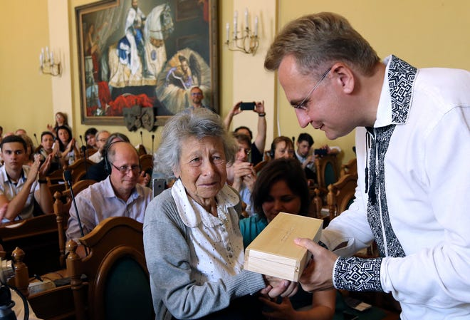 Lviv Mayor Andriy Sadoviy, right, presents a glass copy of an old metal synagogue key to Yanina Hescheles, Polish writer and a Nazi concentration camp survivor, at a ceremony commemorating the 75th anniversary of the annihilation of the city's Jewish population by Nazi Germany in Lviv, Ukraine, Sunday, Sept. 2, 2018. The Ukrainian city of Lviv, once a major center of Jewish life in Eastern Europe, is commemorating the 75th anniversary of the annihilation of the city's Jewish population by Nazi Germany and honoring those working today to preserve that vanished world. The commemoration comes amid a larger attempt in Ukraine to preserve the memories of the prewar Jewish community.