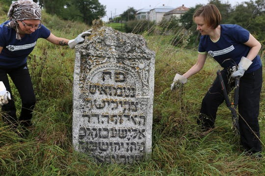 In this photo taken on Aug. 29, 2018, volunteers clean an old Jewish cemetery in Rohatyn, the site of a Jewish Heritage project, close to Lviv, Ukraine, a few days before the 75th anniversary of the annihilation of the city's Jewish population by Nazi Germany. The Ukrainian city of Lviv, once a major center of Jewish life in Eastern Europe, is commemorating the 75th anniversary of the annihilation of the city's Jewish population by Nazi Germany and honoring those working today to preserve that vanished world. The commemoration comes amid a larger attempt in Ukraine to preserve the memories of the prewar Jewish community.