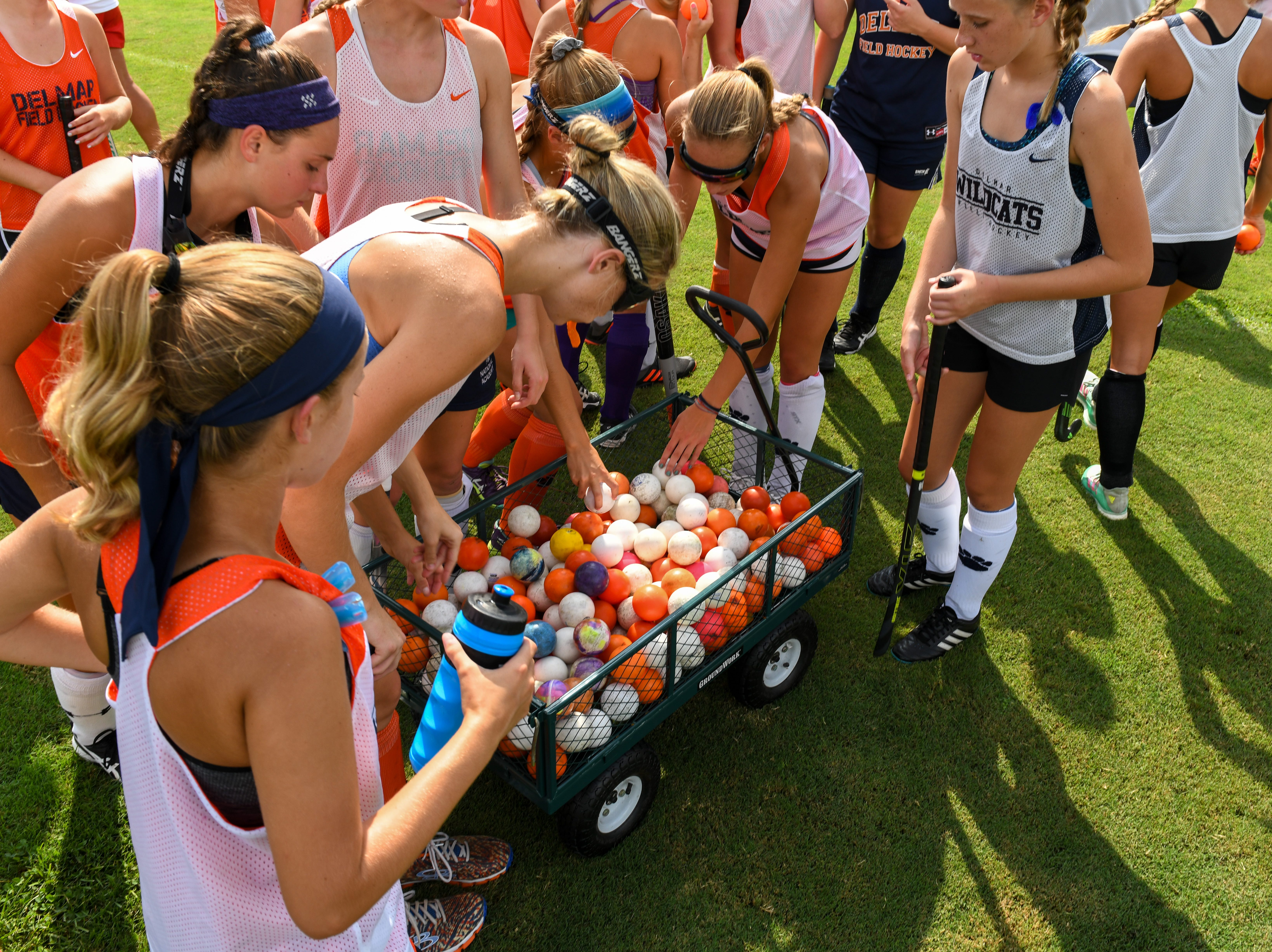 The Delmar field hockey team grabs balls before running drills at practice on Wednesday, Sept. 5.