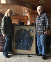 Felton and Rita Pruett pose with a framed suit he once wore to perform with Hank Williams.