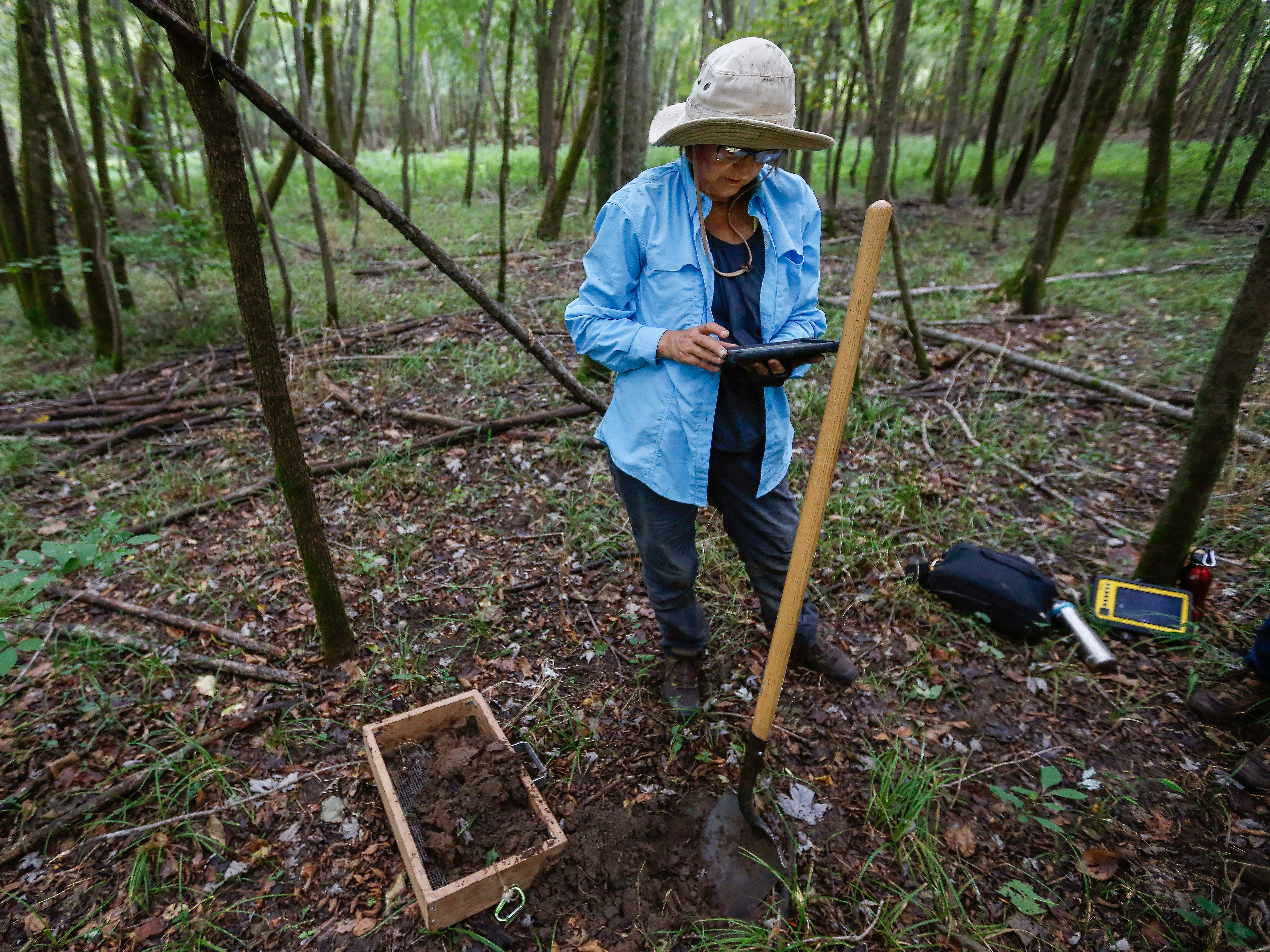 Survey team leader Robin Jorcke notes the GPS coordinates of a hole she dug at a survey site along Lake Taneycomo on Thursday, Aug. 30, 2018.