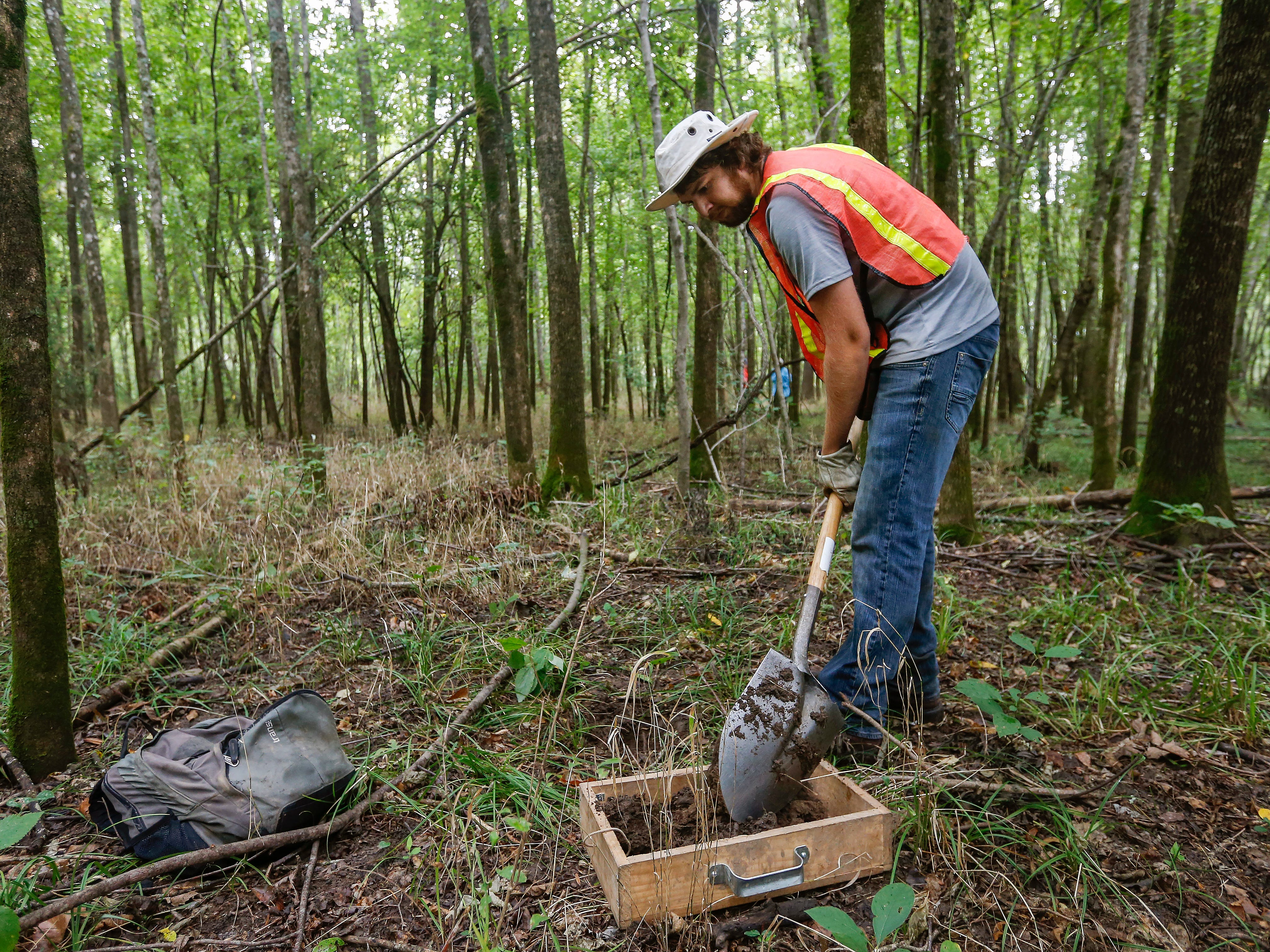 Field technician Alex Koch shovels dirt into a sifting screen at a survey site along Lake Taneycomo on Thursday, Aug. 30, 2018.