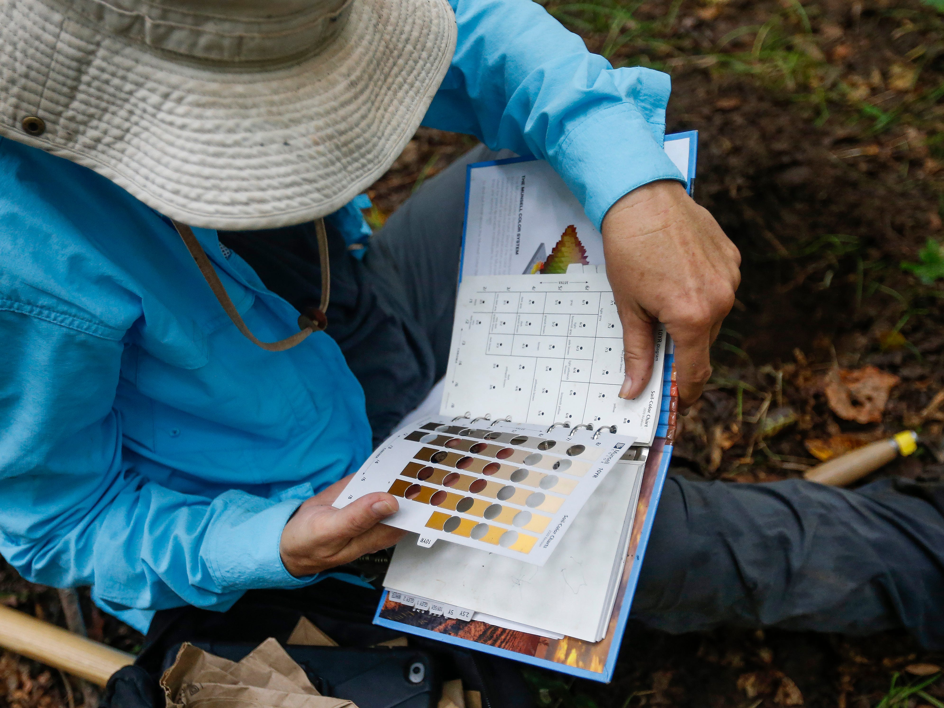 Survey team leader Robin Jorcke notes the color of dirt in a hole she dug at a survey site along Lake Taneycomo on Thursday, Aug. 30, 2018.