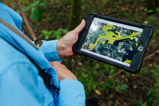 Survey team leader Robin Jorcke checks her GPS while walking toward a survey site along Lake Taneycomo on Thursday, Aug. 30, 2018.