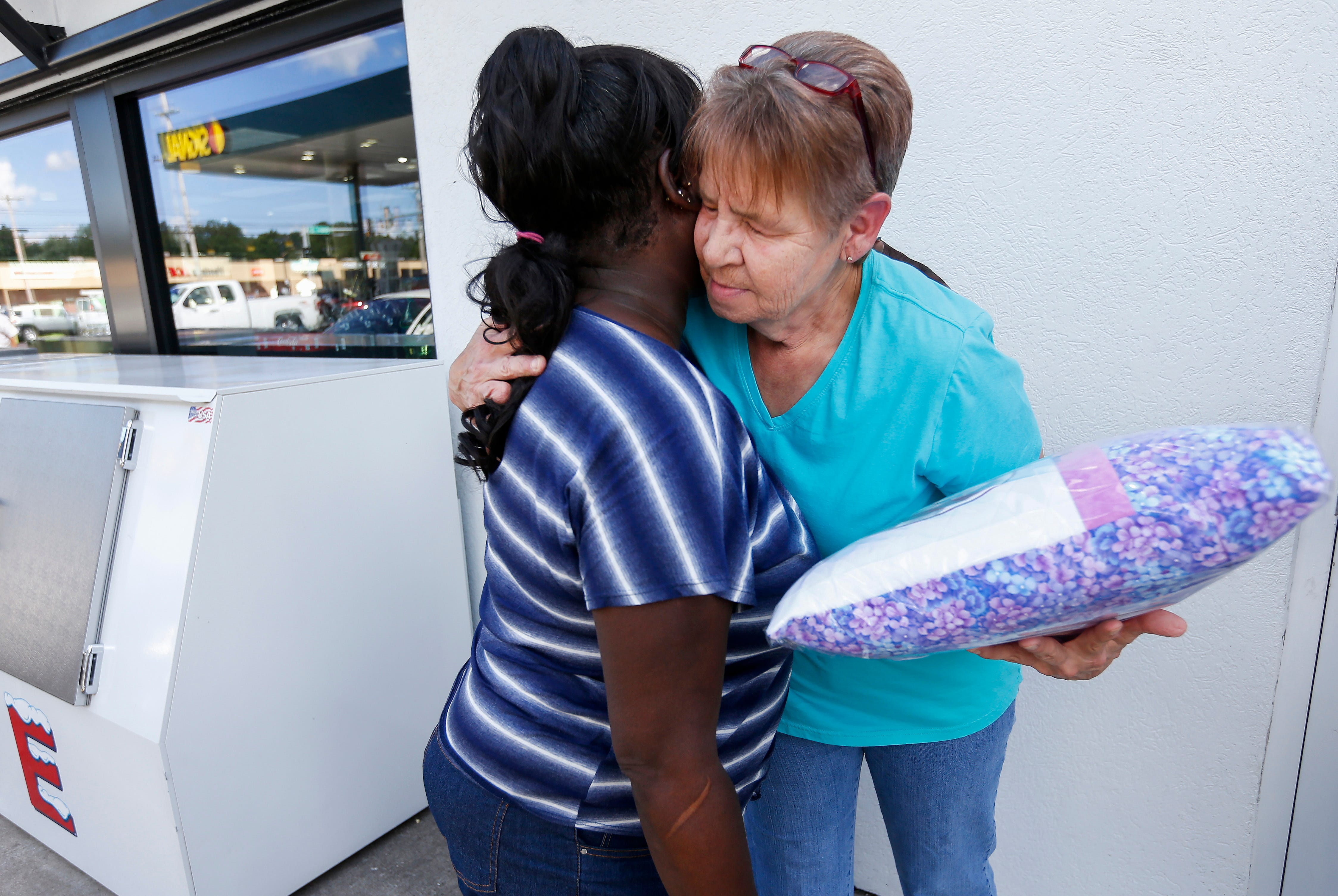Linda Carter, left, the mother of Slyolandra Patterson, hugs Dee Lawson after she was presented with a memory pillow on Wednesday, Sep. 5, 2018. Patterson was found dead with a gunshot wound on Saturday, Aug. 25, 2018 inside a home in the 2600 block of South Fremont Avenue.