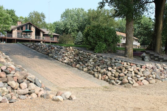 The yard gradually slopes to the waterfront and can be accessed via a paving stone sidewalk.