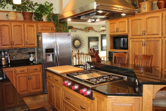 The center point of the kitchen is a large, vented hood that streams down from the vaulted ceiling.