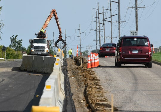 Crews move barricades between traffic lanes in a construction zone on Benton County Road 29 in Sartell in this September 2018 file photo. A new, half-percent sales tax is expected to generate an estimated $1.9 million toward transportation projects in the county.