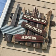 A custom-made sign hangs outside the new Crooked Hinges occasional shop, which is set to open Oct. 11.
