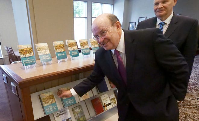 "Quentin L. Cook, a member of The Church of Jesus Christ of Latter-day Saints' Quorum of the Twelve Apostles,  reaches for the ""Saints: The Standard of Truth,"" following a news conference Tuesday, Sept. 4, 2018, in Salt Lake City. Behind him is Dale Renlund. Church leaders unveiled a new narrative book about the faith's early history in the 1800s that follows a recent commitment to transparency by acknowledging the polygamous roots of the faith."