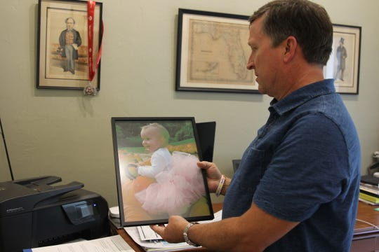 Patrick Conn shows a photo of his daughter McKenzie, who died in 2007 -- just shy of her fourth birthday -- from a blood cancer. He's cycling cross-country to raise awareness and funds for cancer research.