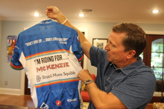Patrick Conn shows his shirt, inscribed with the name of his daughter, McKenzie, who died in 2007 from a type of lymphoma. He's cycling to raise funds for cancer research.
