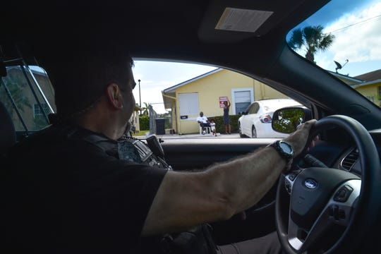 """City of Stuart Police Department Road Patrol Officer Chris Ruediger gets a wave from residents on Wednesday, Aug. 29, 2018, while cruising the streets of East Stuart. """"My job is to create and build community relations within the East Stuart community,"""" Ruediger said."""