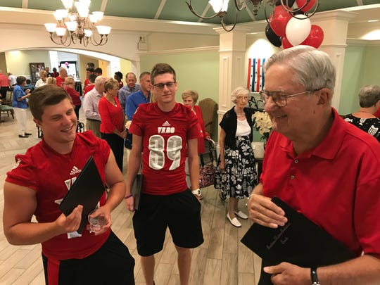 Nick Celidonio (from left), Ben Yurigan and Bill Churchill wait to be seated for dinner Aug. 10 at Indian River Estates, a retirement community in Vero Beach. The Vero Beach High football players visited with residents during a pre-season pep rally.