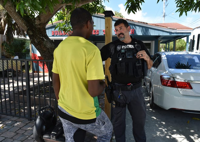 """City of Stuart Police Department Road Patrol Officer Chris Ruediger talks with a teen suspended from school for the day, wandering the roadway near the Building Bridges To Youth building along SE Church Street on Wednesday, Aug. 29, 2018, in the neighborhood of East Stuart. """"There is a program called ALTOSS, and it's Alternative To Out of School Suspension,"""" Ruediger, said. """"So rather than being suspended from school and hanging out on the streets for the day, they go to the rec center and they talk there about whatever it is that they did that was wrong, and they have adults there that can kind of mentor them."""""""