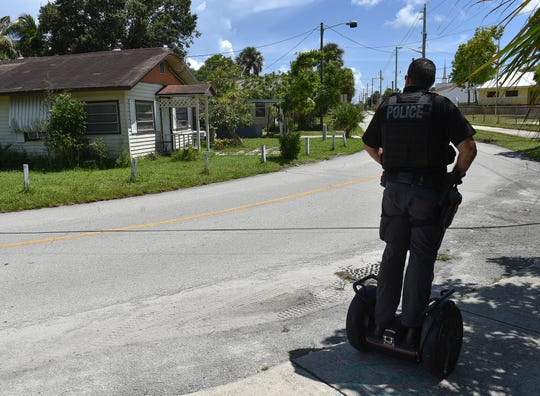 Traveling along the perimeter of the neighborhood of East Stuart on Wednesday, Aug. 29, 2018, Stuart Police Department Road Patrol Officer Chris Ruediger, rolls past a condemned home (left) in the 400 block of SE Church Street, while patrolling the neighborhood on a Segway scooter.