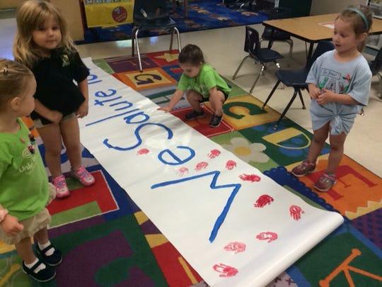 Addisyn Fry, Sydney Kelleher, Sienna Rogers, and Molly Bradley work on their banner.