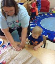 Chesterbrook's Michelle Collins helps Daxton Urquhart make a handprint.