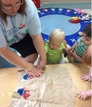 Ms. Michelle Collins helps Capen Boyd make a handprint, while Sebastian Infante waits his turn.