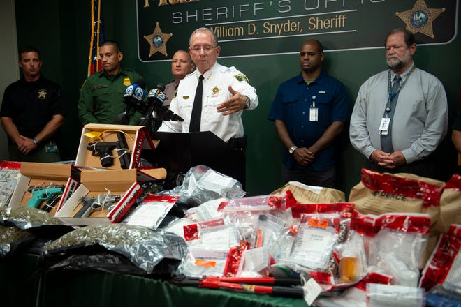 """Martin County Sheriff William Snyder (center) presents a variety of drugs, weapons and money confiscated over a two-day interdiction on I-95 last week during a news conference Wednesday, Sept. 5, 2018, at the Martin County Sheriff's Office in Stuart. Snyder said multiple agencies worked together to arrest 47 people. """"This is very disturbing. This is very dangerous,"""" Snyder said, noting that there have been 25 overdose deaths in Martin County this year and that most of the people incarcerated have substance abuse problems. """"If we don't do something about it, it flows more freely up the interstates,"""" he said."""