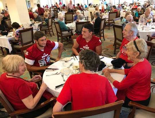 Jack Karshner (left) and Logan Amaral laugh with residents before dinner at Indian River Estates on Aug. 10 during a pre-season pep rally at the community. Players and cheerleaders visit the retirement community every year before the start of the football season.
