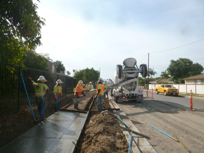 Construction workers are seen in the midst of a sidewalk project on Kenney Street near Oxnard.