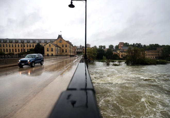 A motorist drives over the Fox River on South Olde Oneida Street in Appleton on Wednesday as rain continues to fall. Wednesday's rains added to already saturated conditions across Wisconsin.