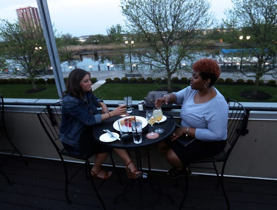 Kelsey Yingling (left) and Nashiya Wright, both of Philadelphia, take a table on the deck at Iron Hill Brewery at Wilmington's Riverfront.