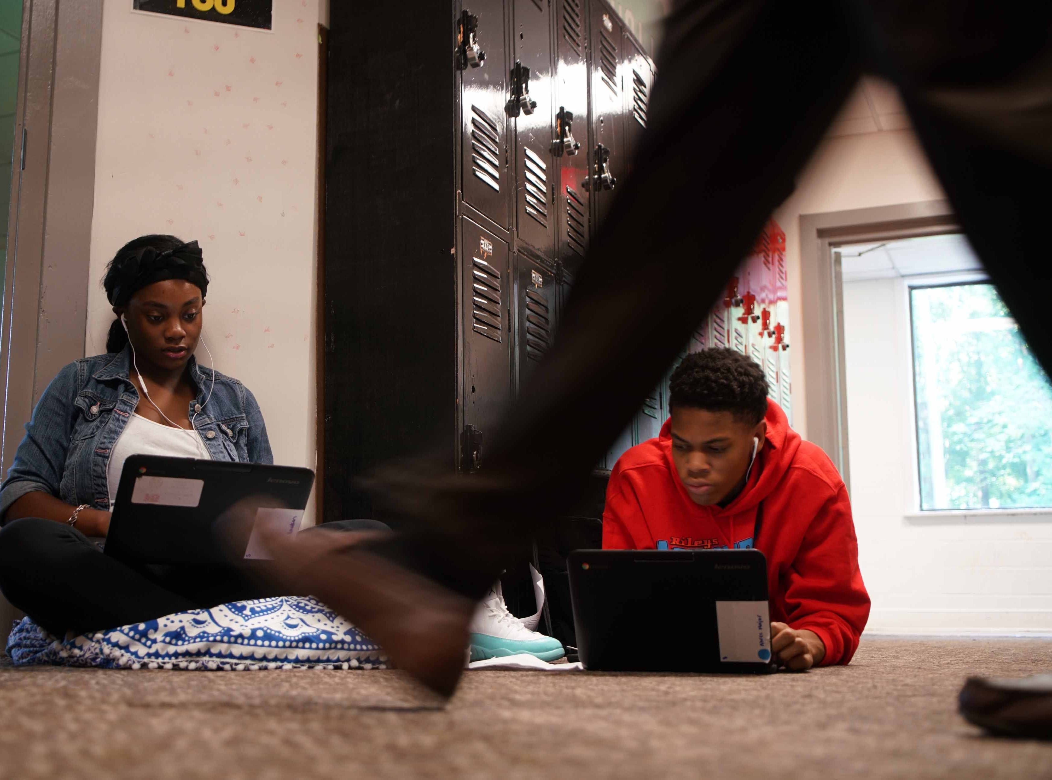 Jilisa Leibert, 15, a freshman, and Christopher Miller, 17, a senior at the Design Thinking Academy, work on a class assignment in the hallway.