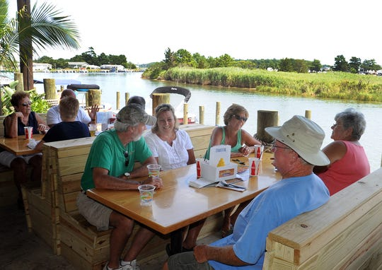"""The Paradise Grill located on Indian River Bay in the Pot Nets Bayside Community off Long Neck Road near Millsboro. It features open air dining and socializing in their many dining area and """"Tiki Bars."""" You can drive your golf cart or dock your boat at their own marina to enjoy your day in a tropical setting that also features a large stage for live bands."""