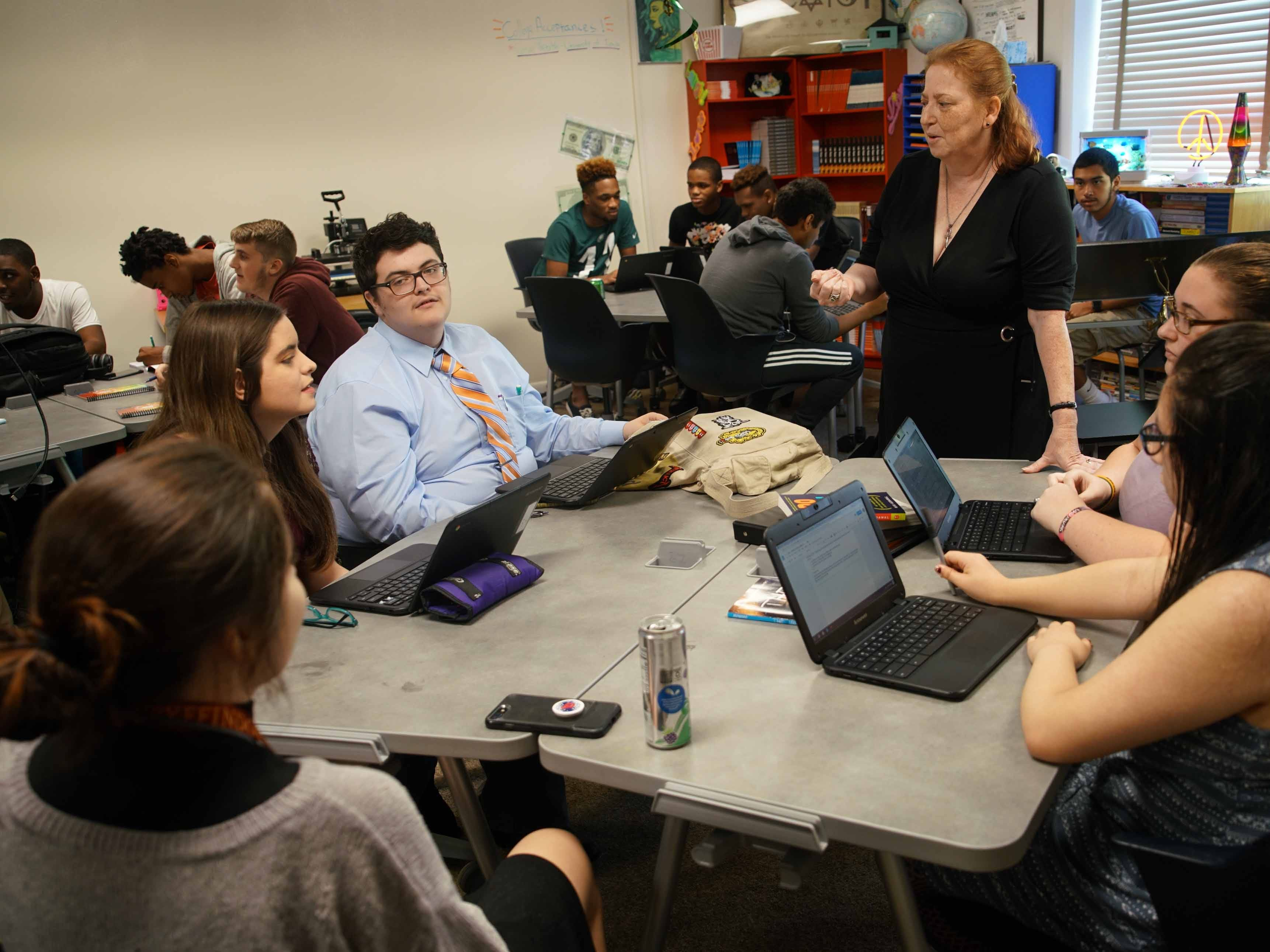 Nancy Marvel, a entrepreneur teacher at the Design Thinking Academy, talks with students taking her advanced marketing class.