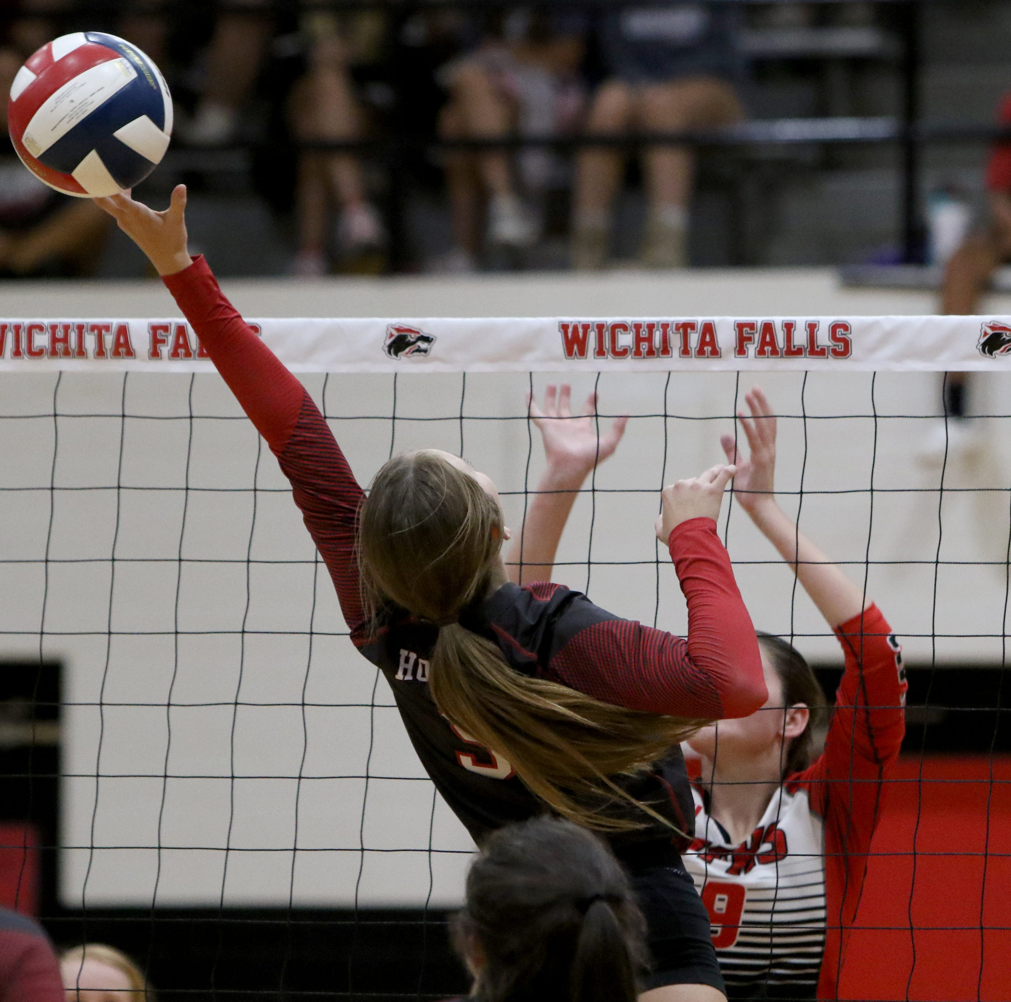 Holliday's Brittany James tips the ball over to Wichita Falls High School Tuesday, Aug. 4, 2018, in the Wichita Falls High School gym.