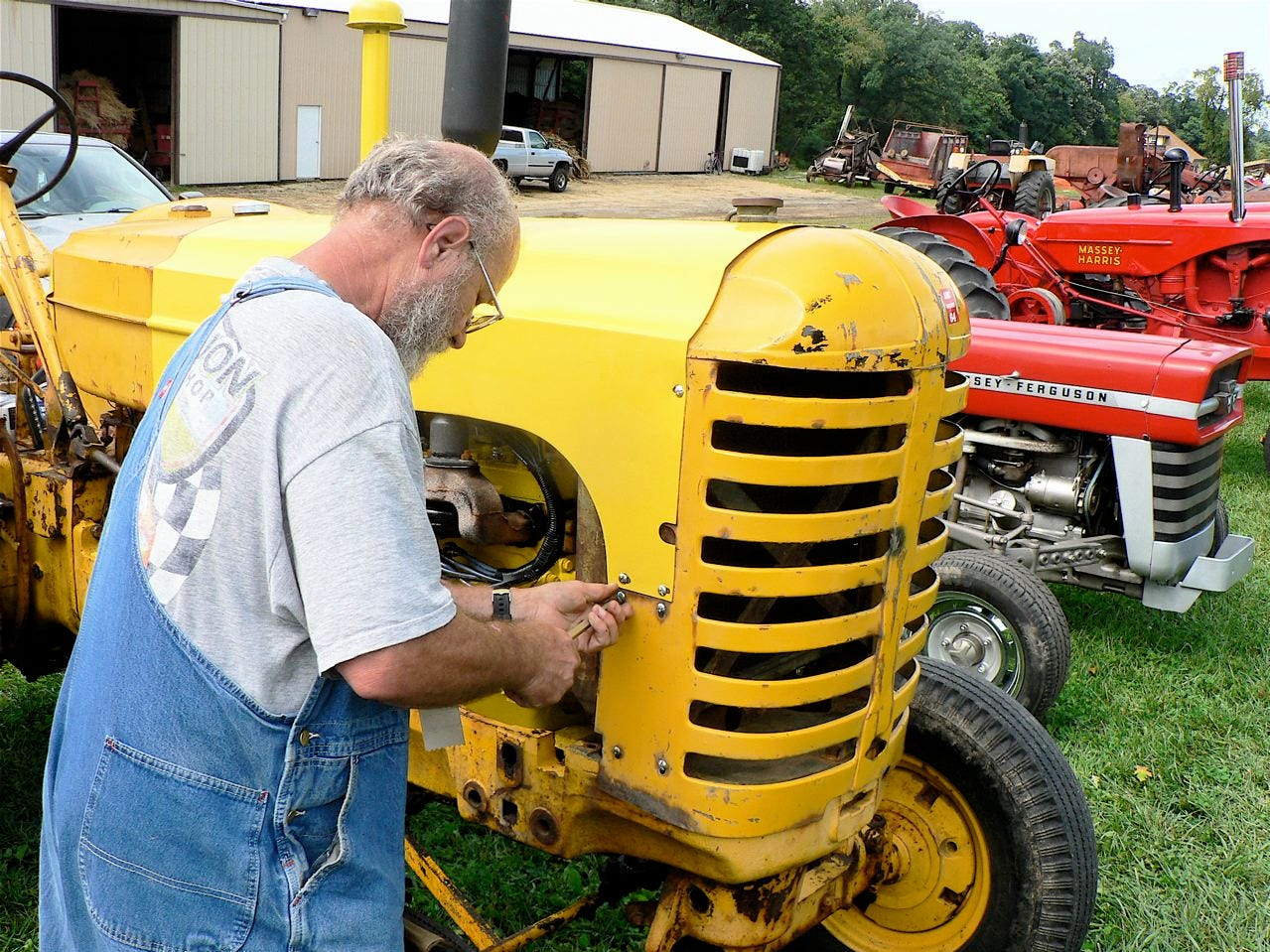 Dave Willie of Necedah tightens a bolt on a shield on his rare yellow Massey industrial tractor.