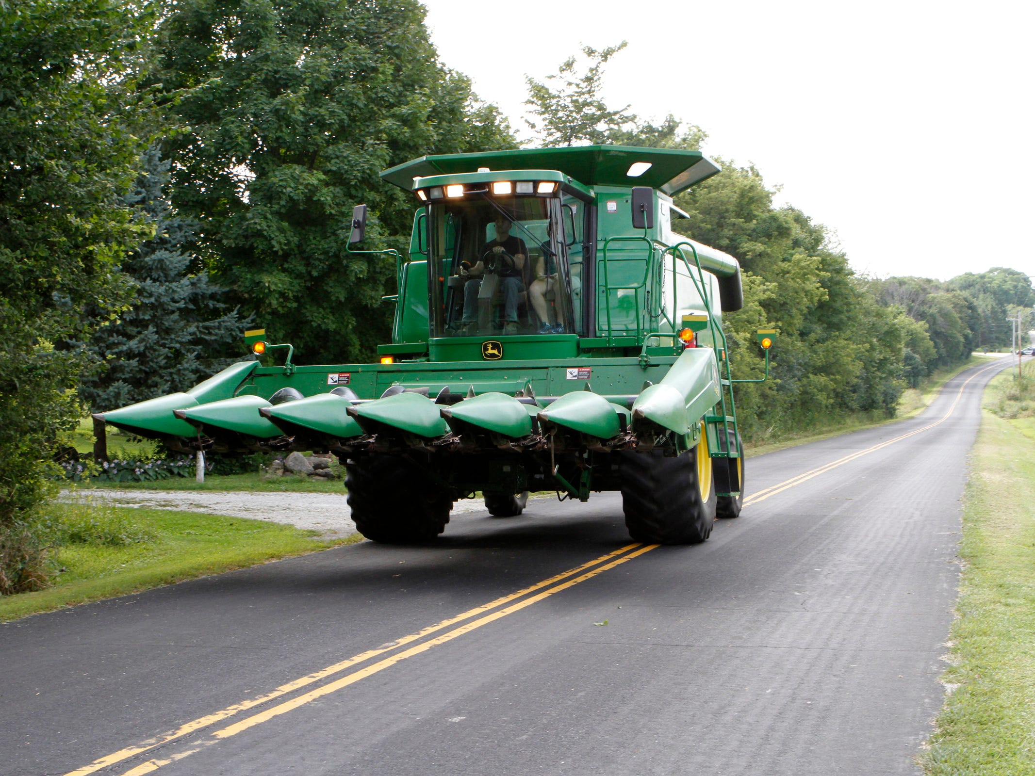 Wide farm equipment extends over the centerline on narrow roads.