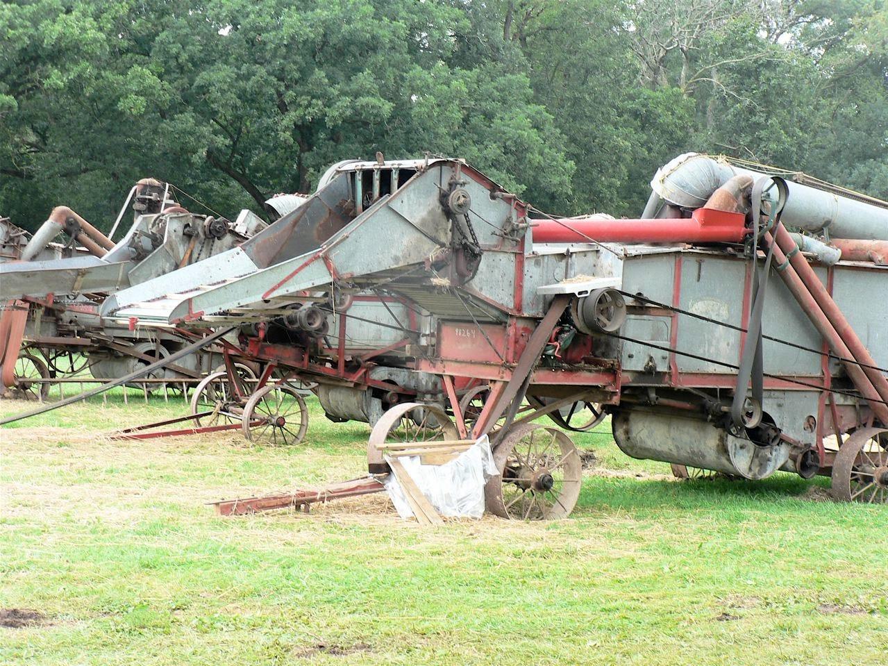 A line of threshing machinery stands quiet under rain threatening skies.