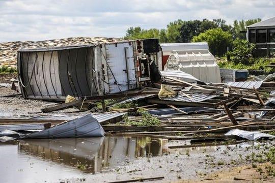 A grain semi trailer lies tipped over amongst a pile of debris Wednesday, August 29, 2018 at W12072 Hemp Road near Waupun, Wisconsin.