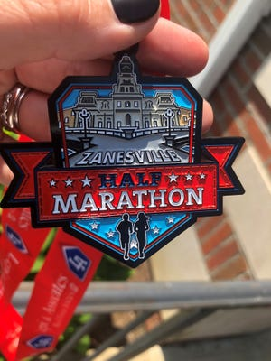 The finishing medals for the first Zanesville City Half Marathon highlight the Y Bridge and Muskingum County Courthouse.