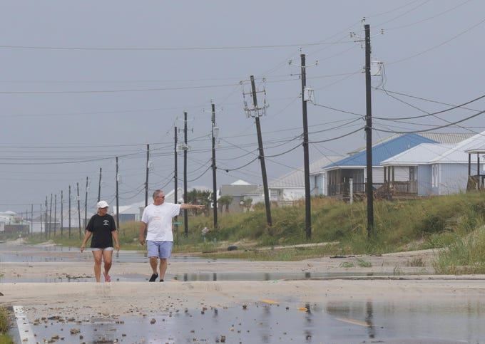 Susan and Bill Jones walk through a road partially covered with sand from Tropical Storm Gordon on Sept. 5, 2018, in Dauphin Island, Ala.