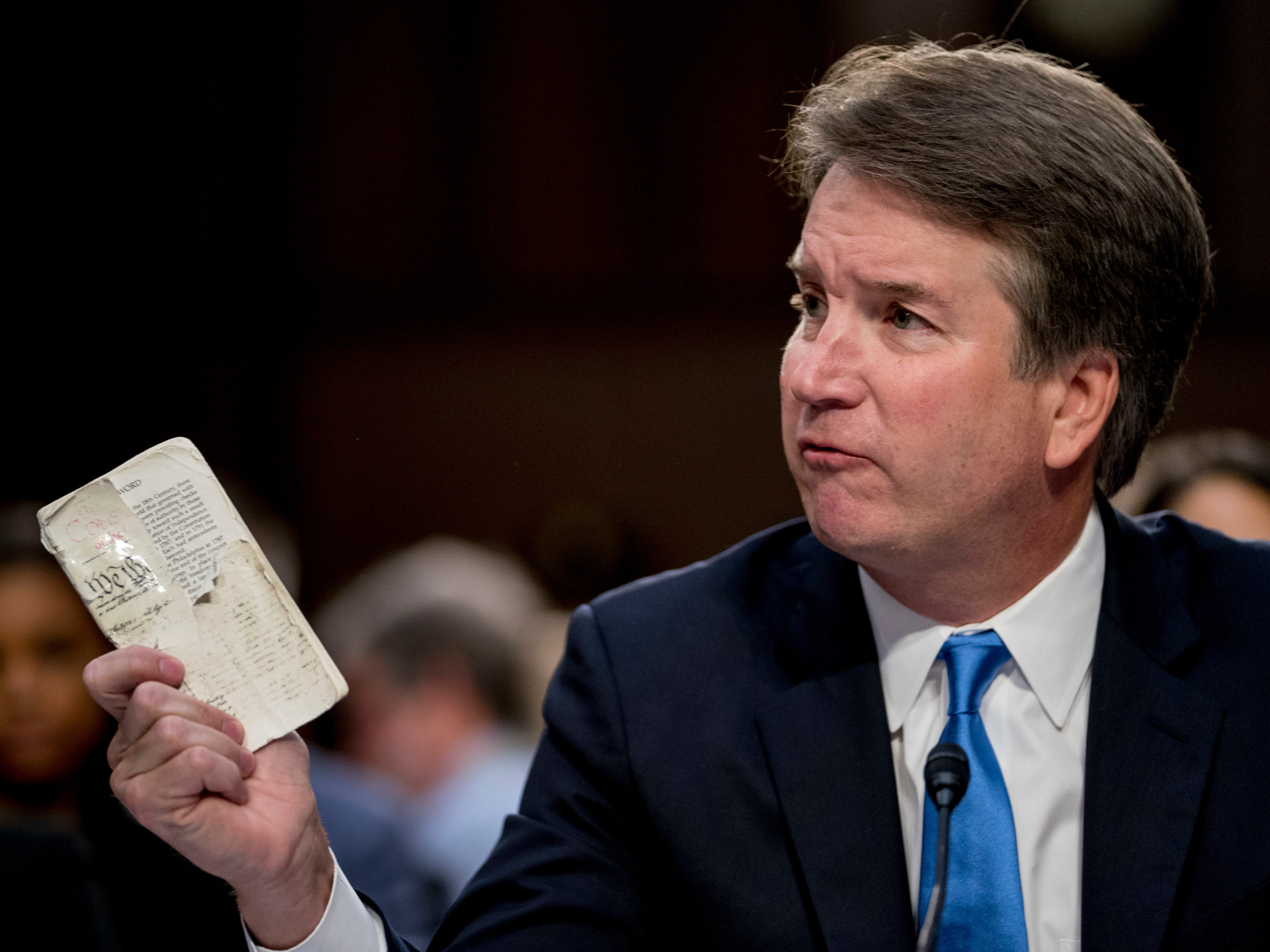 President Donald Trump's Supreme Court nominee, Brett Kavanaugh, a federal appeals court judge, holds up a worn copy of the Constitution of the United States as he testifies before the Senate Judiciary Committee on Capitol Hill in Washington, Wednesday, Sept. 5, 2018, for the second day of his confirmation to replace retired Justice Anthony Kennedy. (AP Photo/Andrew Harnik) ORG XMIT: DCAH120