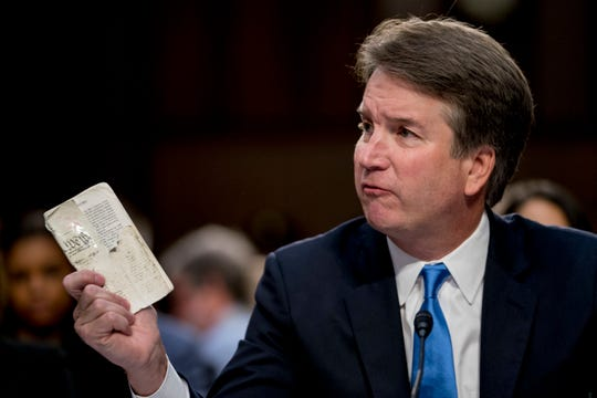 President Donald Trump's Supreme Court nominee, Brett Kavanaugh, a federal appeals court judge, holds up a worn copy of the Constitution of the United States as he testifies before the Senate Judiciary Committee on Capitol Hill in Washington Sept. 5, 2018.