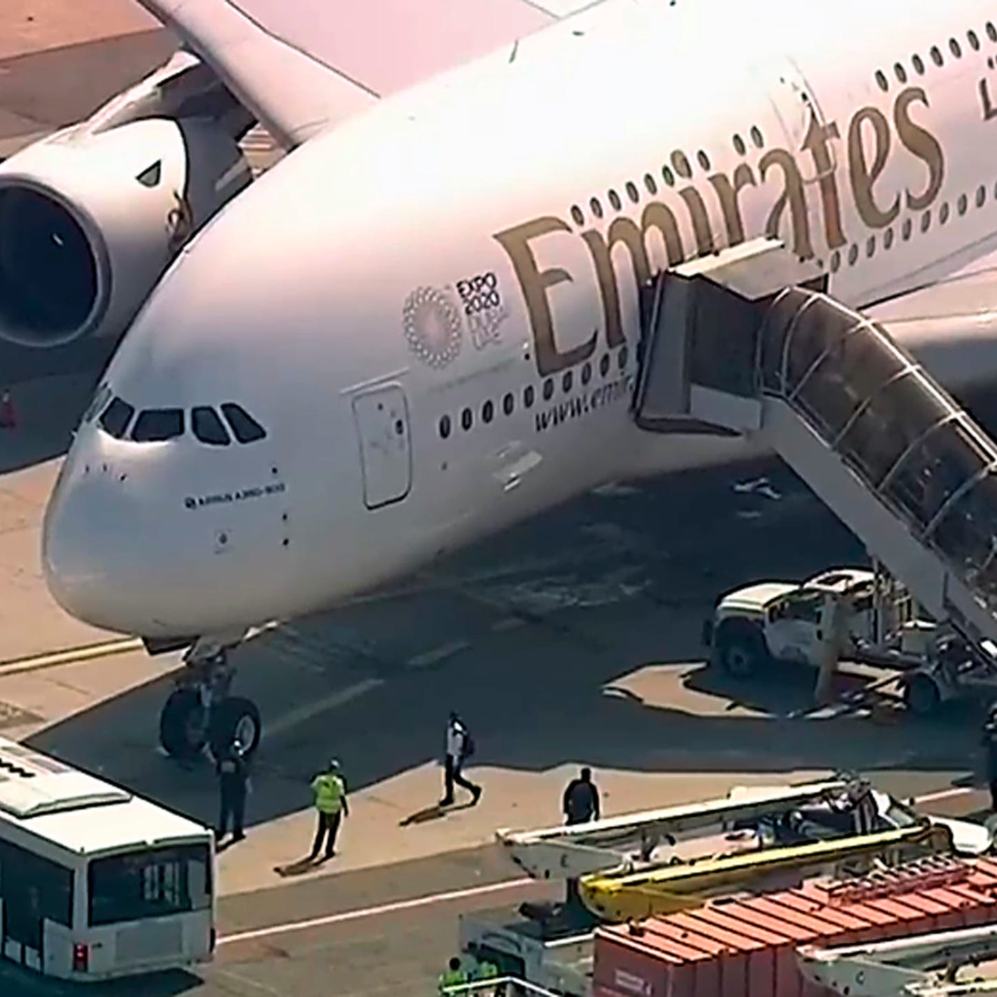 In this frame from video, a person walks off an Emirates plane at JFK International Airport to a waiting bus on Wednesday, Sept. 5, 2018, in New York, as emergency response crews gather outside the plane amid reports of ill passengers aboard a flight from Dubai. (WABC 7 via AP) ORG XMIT: NYR102
