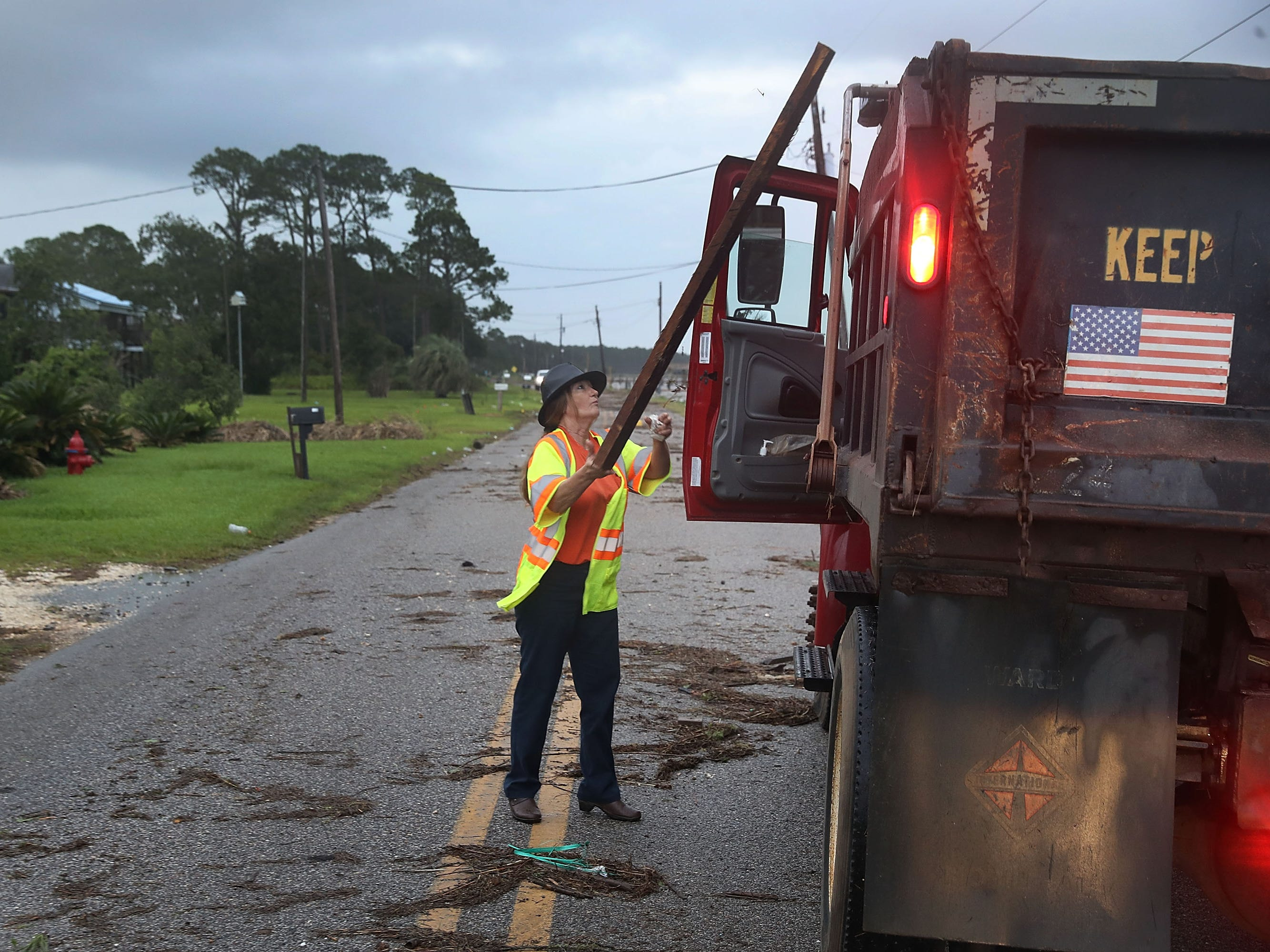 Wanda Williams from the Mobile County government cleans up debris left behind by Tropical Storm Gordon as it passed through the area on Sept. 5, 2018 in Bayou La Batre, Ala.