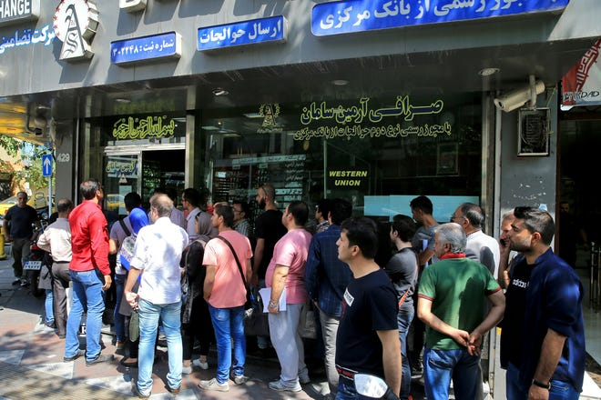 People line up in front of a currency exchange shop to buy U.S. dollars and euros, in downtown Tehran, Iran, Wednesday, Sept. 5, 2018. The Iranian rial fell Wednesday to its lowest rate on record and saw worried residents of Tehran line up outside of beleaguered moneychangers, part of a staggering 140-percent drop in the currency's value since America pulled out of the nuclear deal only four months ago. (AP Photo/Ebrahim Noroozi) ORG XMIT: ENO104