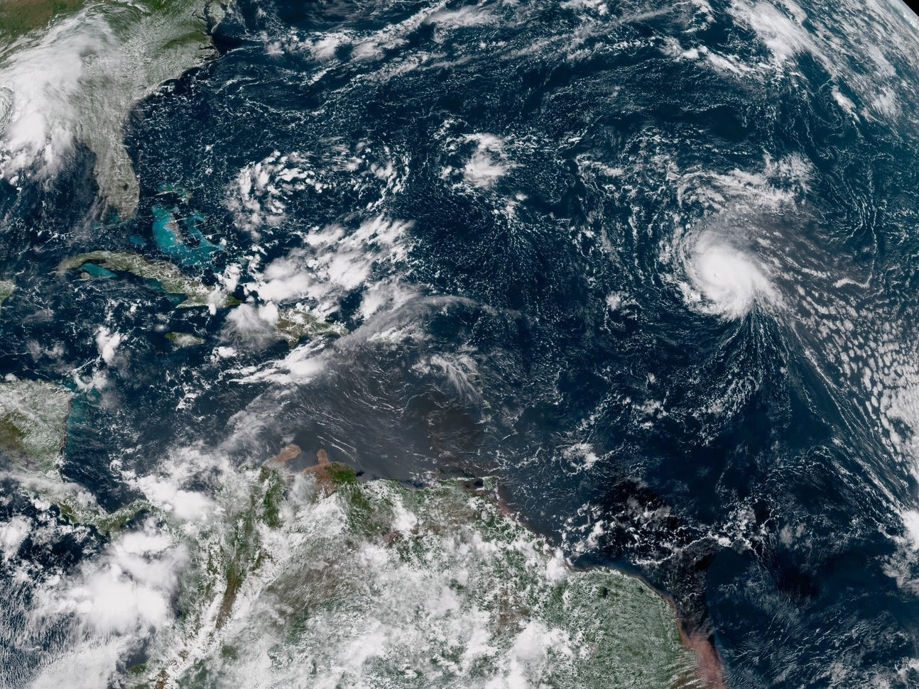 A satellite image shows Hurricane Florence (right) spinning in the central Atlantic Ocean. The U.S. East Coast is in the upper left of the image.